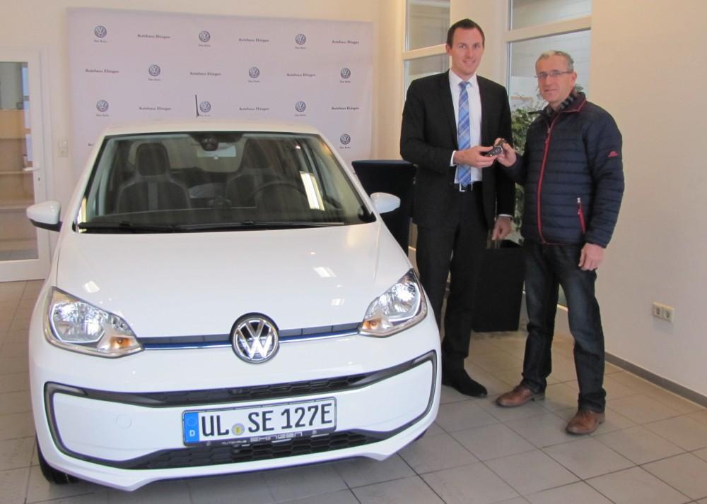 Rolf Schmid von der Stadtverwaltung nimmt von Michael Klumpp vom Autohaus Ehingen das neue E-Fahrzeug entgegen.